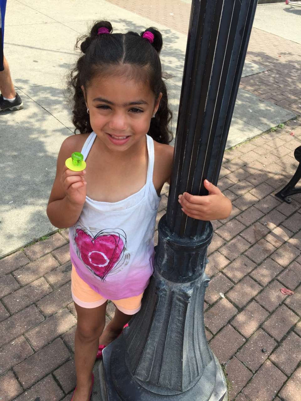 girl with 2 ponytails holding streetlamp with green ring pop and desigual kids heart tank top