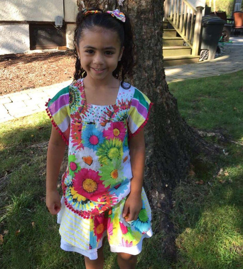 Girl in backyard with Desigual kids printed sunflower tshirt with pom pom trim on sleeves