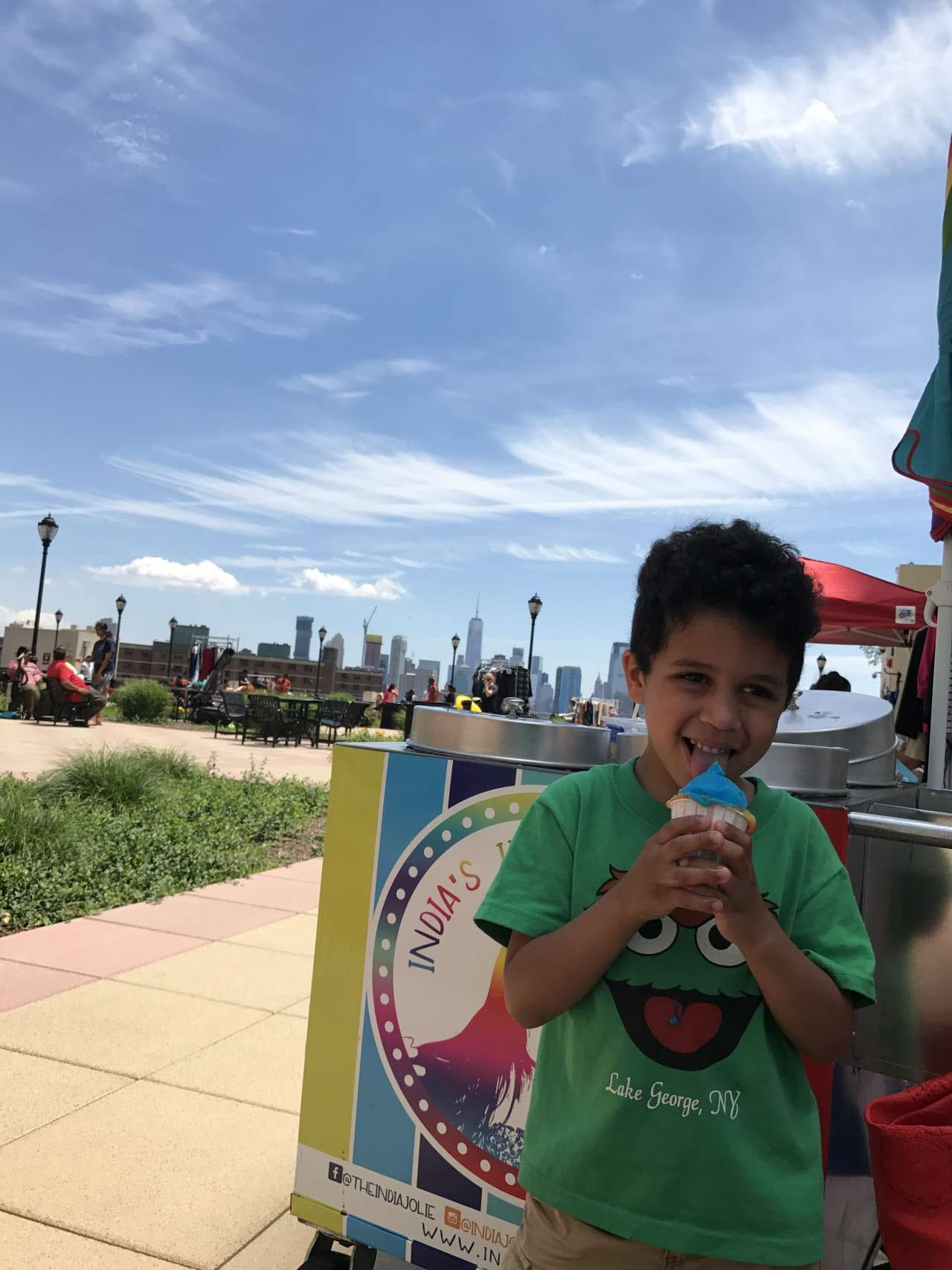 Litle boy with oscar the ground tshirt standing in front of India's Italian Ice cart smiling holidng a blue Italian Ice in his hand with views of NYC in the background