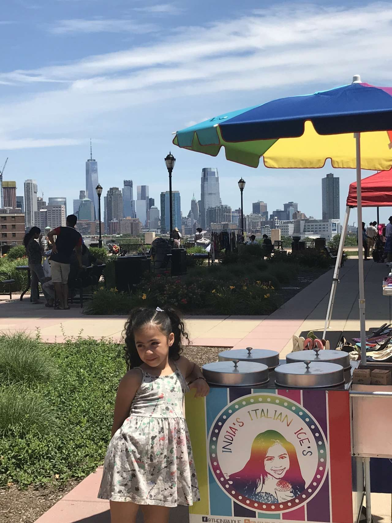 girl leaning on India's Italian Ice Cart with view of NYC in the background on a promenade