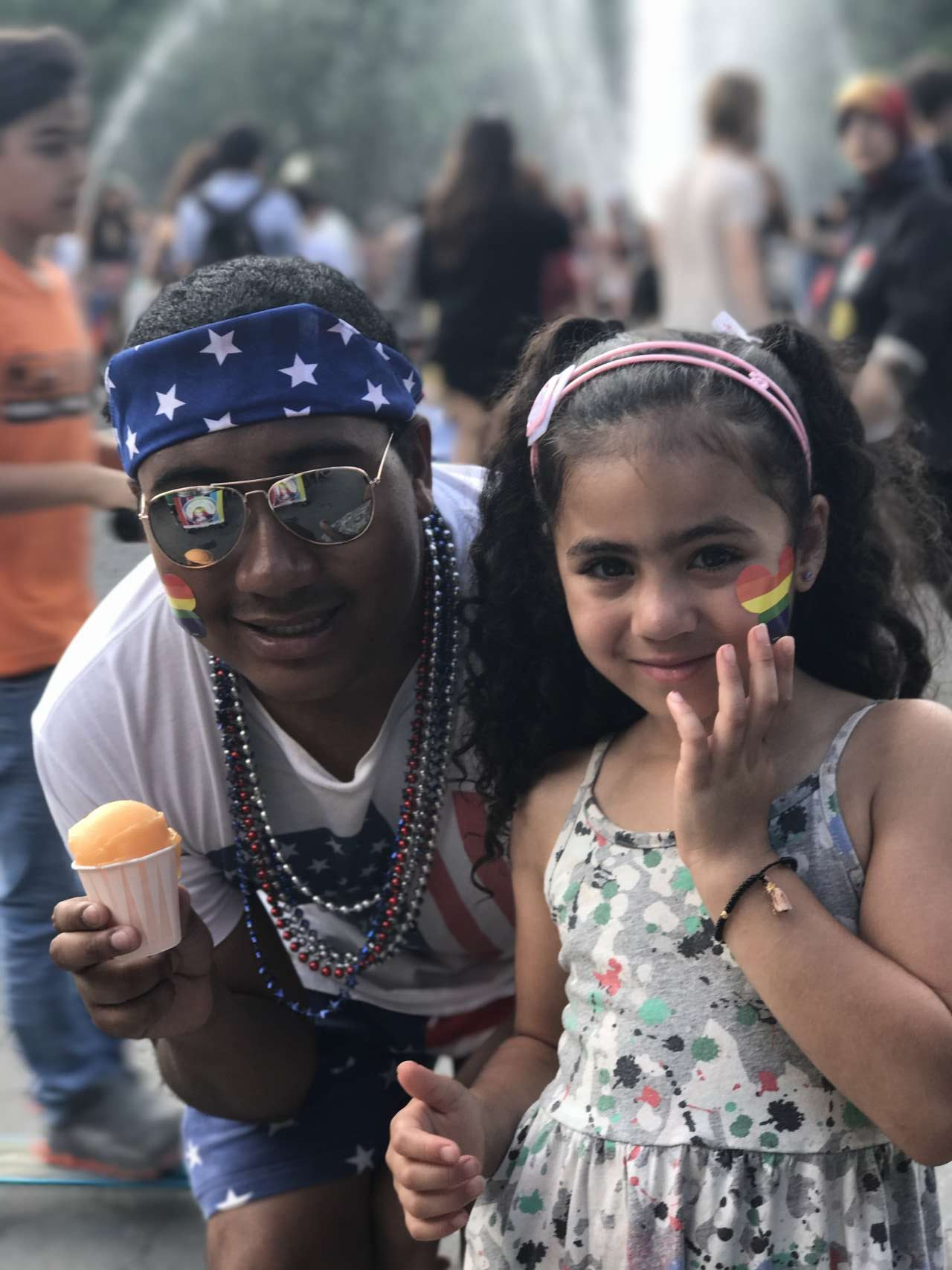 Man with bandana, sunglasses and rainbow heart sticker on face holding a mango italian ice next to girl, India Jolie with rainbow heart sticker on face wearing printed dress with fountain in background