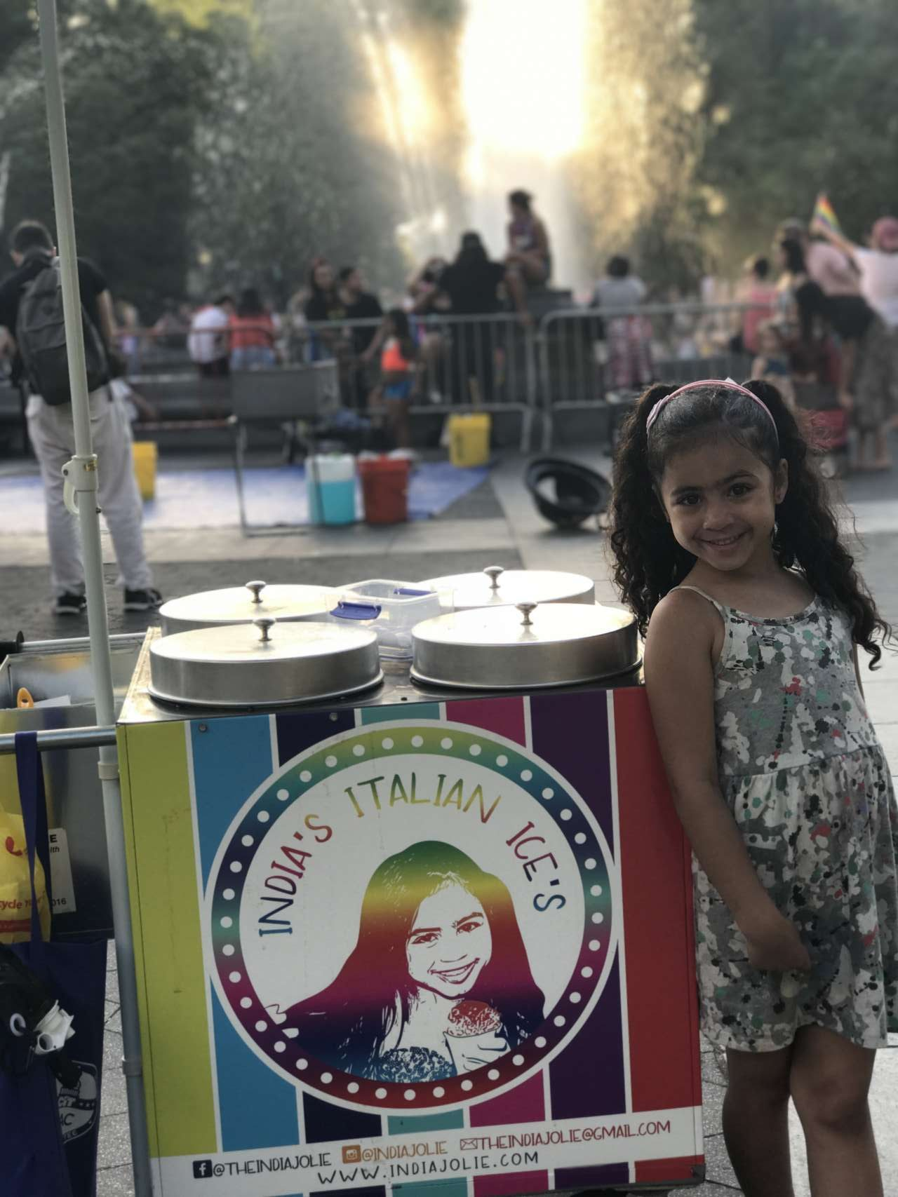 girl India Jolie in printed dress standing next to her rainbow Italian Ice cart in Washington Square Park