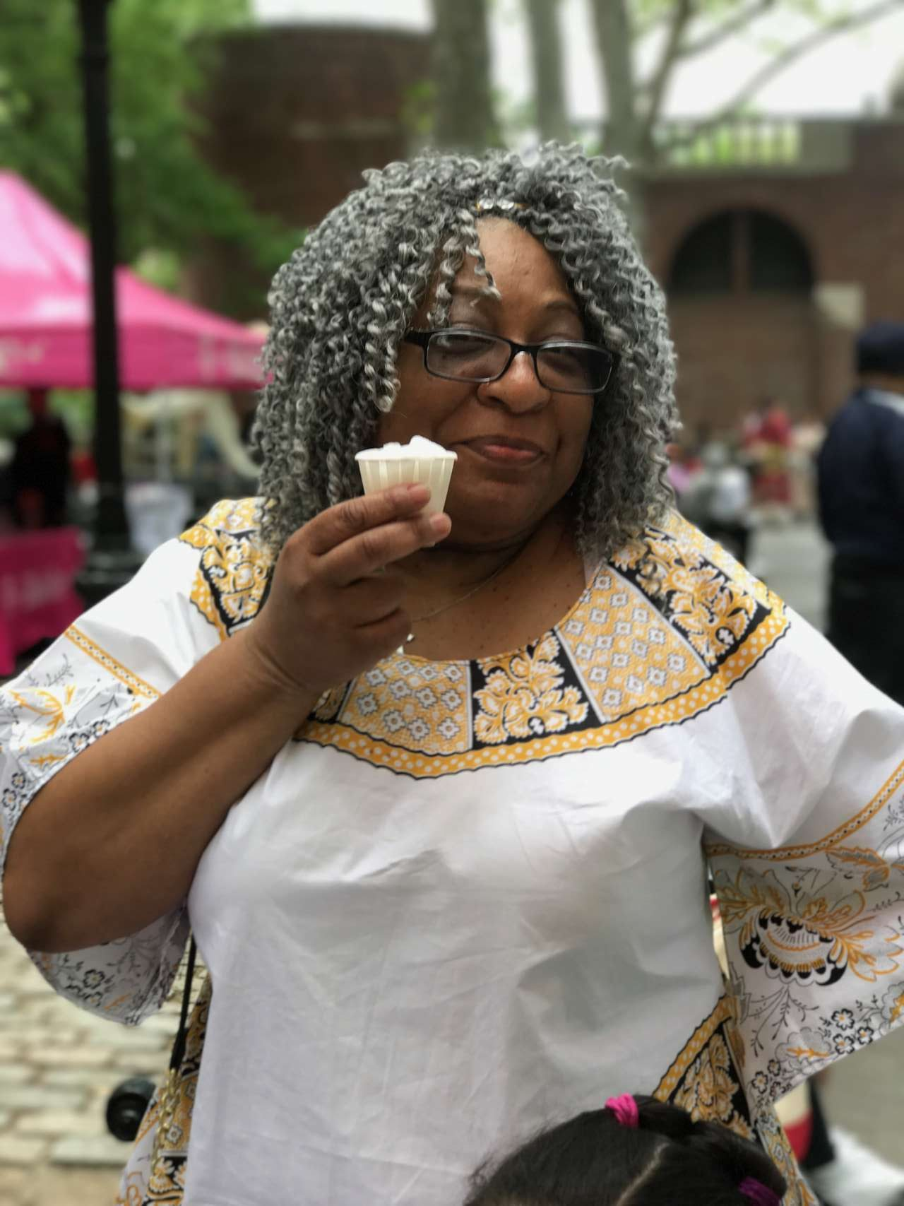 older woman smiling with grey spiral curls in white african dress with gold and black trim smiling and holding lemon italian ice
